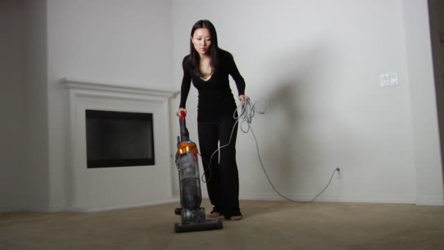 vidéos et rushes de la ws woman vacuuming carpet in empty room in new house / los angeles, california, usa - cable
