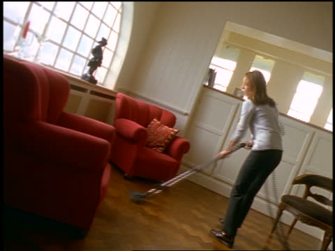 Woman vacuuming hardwood floor in living room