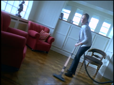 BLUE woman vacuuming hardwood floor in living room