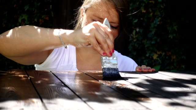 Woman varnishing a self-made pallet table.