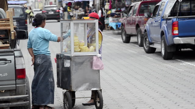 MS Woman vendor on street selling fruit and talking with customer / Otavalo, Ecuador