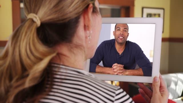 vidéos et rushes de woman video calling black male friend with tablet inside living room - pavé tactile