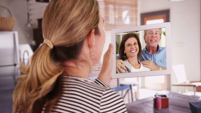 vidéos et rushes de woman video calling parents or family members with tablet from kitchen - voip