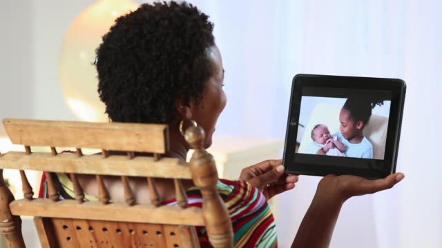 ms woman video chatting with daughter and baby on tablet computer / richmond, virginia, usa - video conference stock videos and b-roll footage