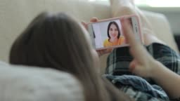 Woman video chatting with her friend at home