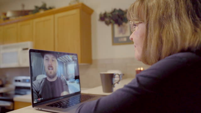a woman video chatting with her son during self quarantine, social distancing - adult stock videos & royalty-free footage