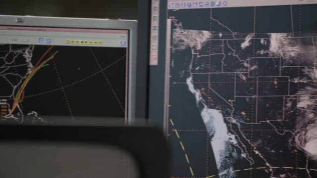 A woman views satellite weather imagery at her desk