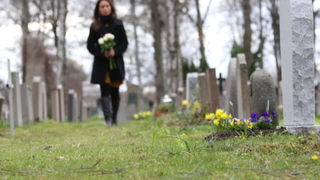 woman visiting a grave at a graveyard - gravestone stock videos & royalty-free footage