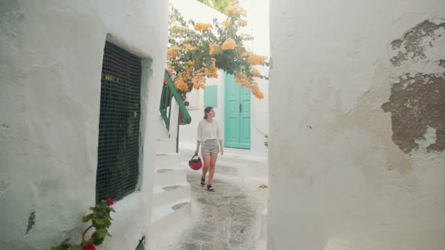 woman visiting mikonos town streets in greece. - mykonos stock videos & royalty-free footage