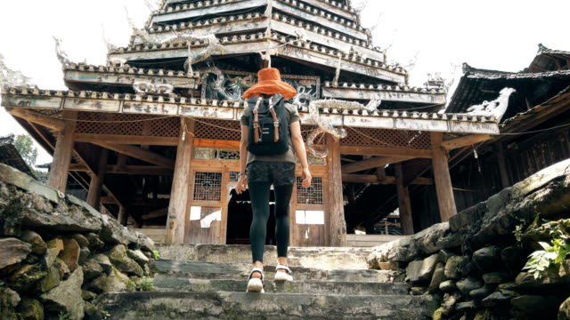 woman visting in huanggang dong village, guizhou, china - temple building stock videos & royalty-free footage