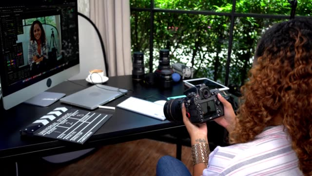 woman vlogger holding camera for filming a movie or a video blog in studio office. freelance concept . - freelance work stock videos & royalty-free footage