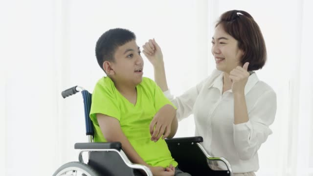 woman volunteer encouraging and playing with  cerebral palsy boy at disabled shelter - cerebral palsy stock videos & royalty-free footage
