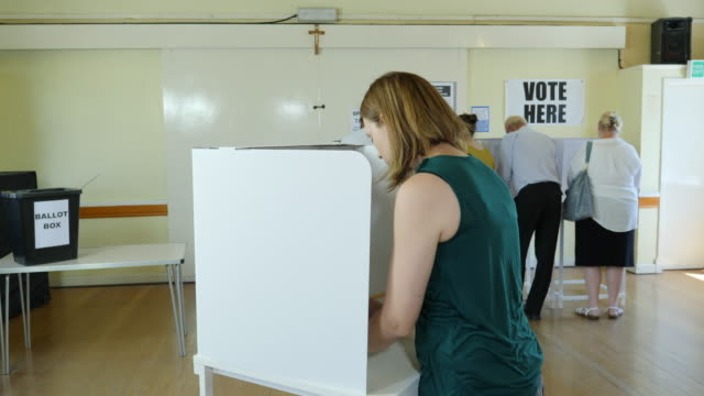 4K DOLLY: Woman voting at booth at Polling Place. Elections
