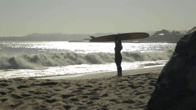 ws woman w/ surfboard running into the ocean - カリフォルニア州サンタクルーズ点の映像素材/bロール