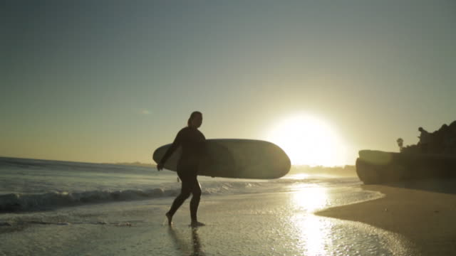 slo mo woman w/ surfboard walking on beach at sunset - santa cruz california stock videos and b-roll footage