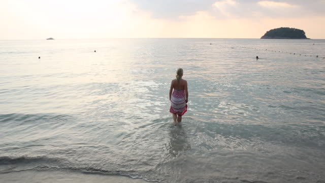 Woman wades into tropical sea, looks towards sunrise