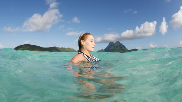 Woman wading in ocean in Tahiti squeezing wet hair / Bora Bora, French Polynesia