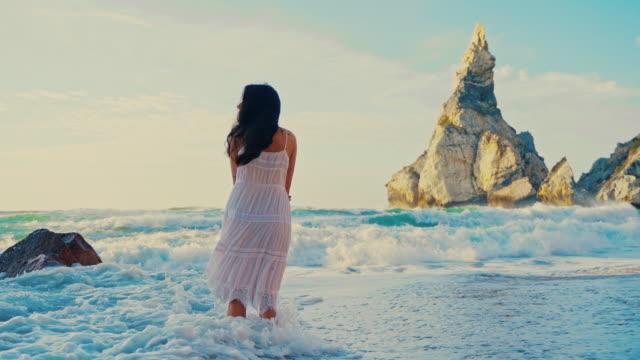 ws pov woman wading in waves at praia da ursa beach in portugal - white dress stock videos & royalty-free footage