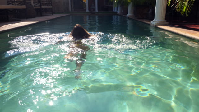 vídeos de stock e filmes b-roll de ts woman wading into pool at hotel during vacation - spa