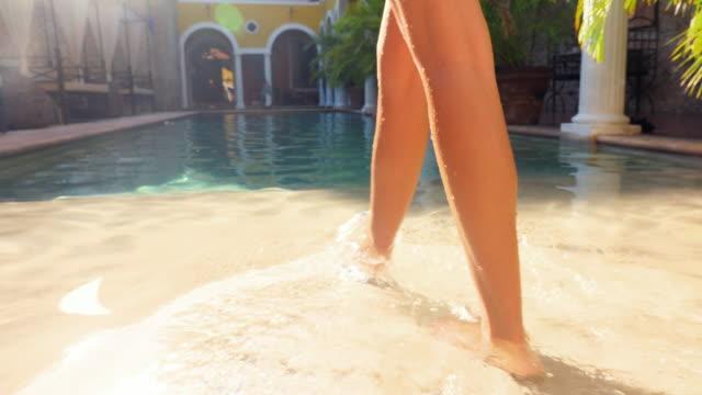 stockvideo's en b-roll-footage met ts woman wading into pool in courtyard of boutique hotel - de volgende stap