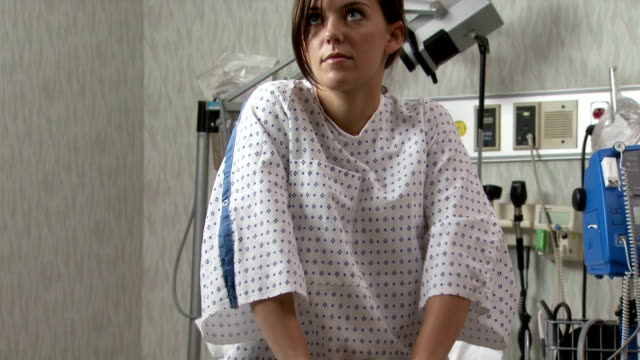 woman waiting anxiously in hospital gown - untersuchungskittel stock-videos und b-roll-filmmaterial