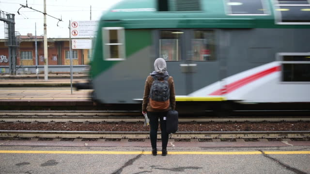 woman waiting at railroad station platform - ferrovia video stock e b–roll