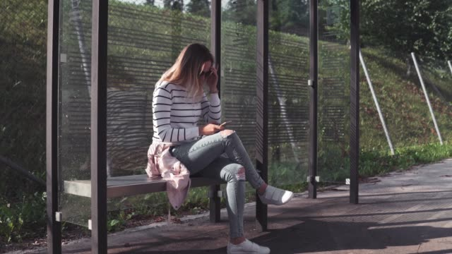 woman waiting for a bus and texting - bus stop stock videos & royalty-free footage