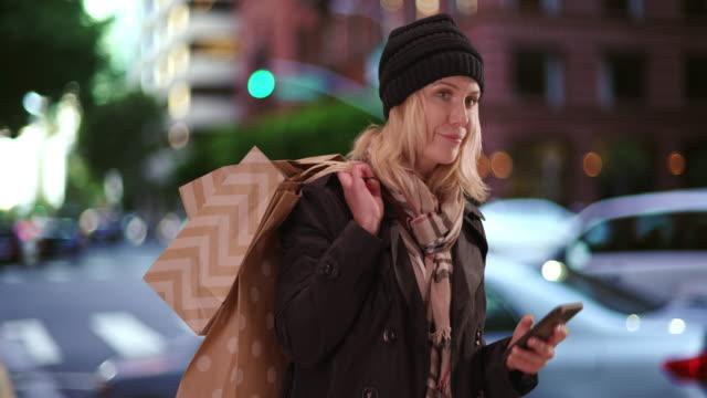 woman waiting for rideshare with shopping bags - 到着点の映像素材/bロール