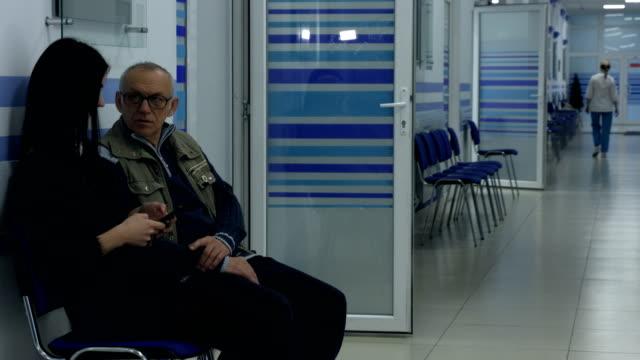 vídeos de stock, filmes e b-roll de mulher esperando no corredor do hospital com seu pai - cuidado pré natal