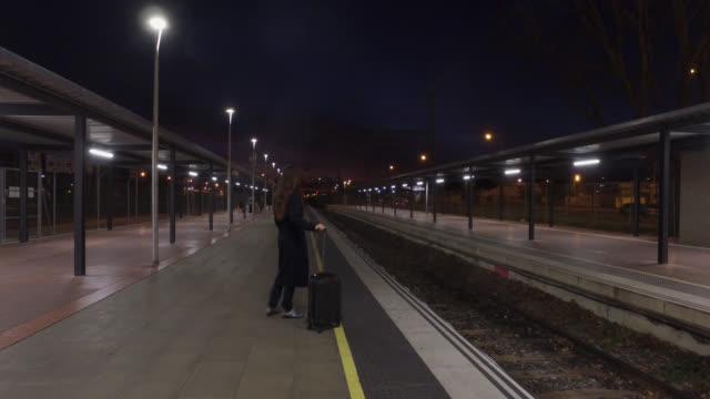 woman waiting on the platform of a train station