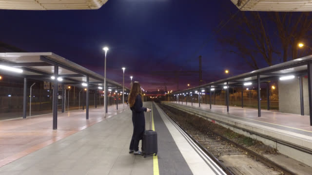 woman waiting on the platform of a train station - one mature woman only stock-videos und b-roll-filmmaterial