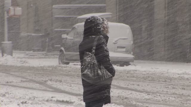 Woman waiting to cross the road during blizzard Available in HD