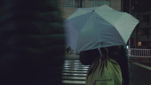 woman waiting to walk with umbrella across a crossroads - protection stock videos & royalty-free footage