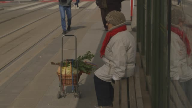 A woman waits for a tram, Warsaw