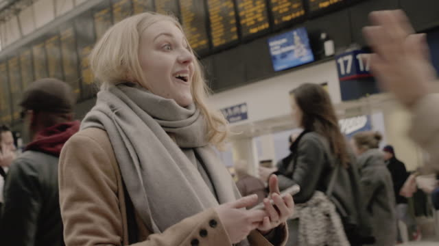 woman waits for friend, she greets and embraces her at the railroad station. - railway station stock videos and b-roll footage