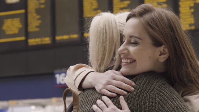 Woman waits for friend to arrive at train station, friend meets her and embraces her.