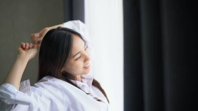 女性は朝、目覚めの体を伸ばす - 起床する点の映像素材/bロール