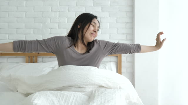 woman wake up refreshed on morning in bedroom - sleeping stock videos & royalty-free footage