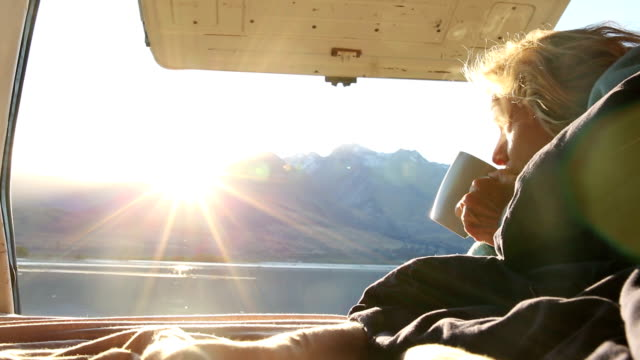 Woman wakes up in camper-van to admire the sun rising over mountain lake