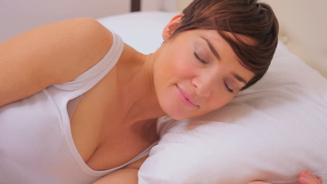 woman waking from on her pillow - hazel eyes stock videos & royalty-free footage