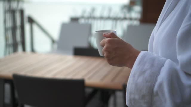 stockvideo's en b-roll-footage met a woman waking in a white bathrobe with a cup of coffee at a tropical island resort. - badjas