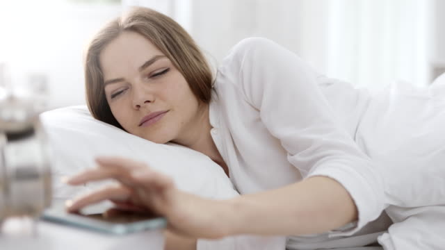 Woman waking up and turning alarm off