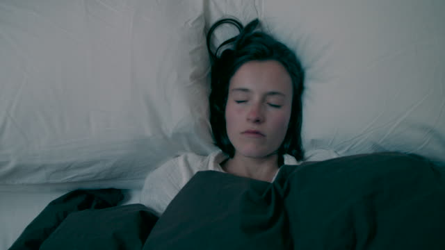 woman waking up in bed - sdraiato video stock e b–roll