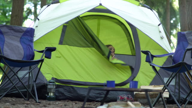 vídeos de stock, filmes e b-roll de woman waking up in tent - cadeira dobrável