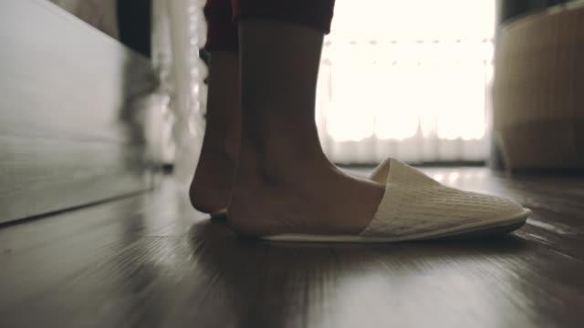朝目覚めた女、足を歩いている女性が窓に行く、スローモーション