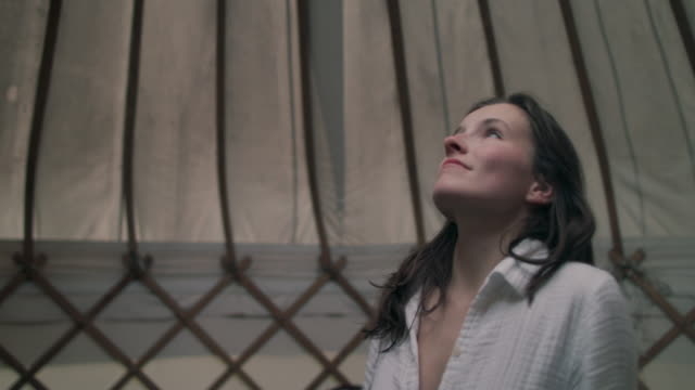 woman waking up in yurt - stillstehen stock-videos und b-roll-filmmaterial
