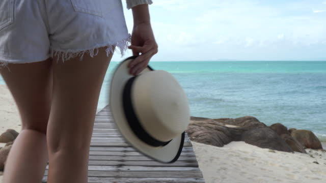 woman walk on the beach seaside the environment bright and clear. - bikini stock videos & royalty-free footage