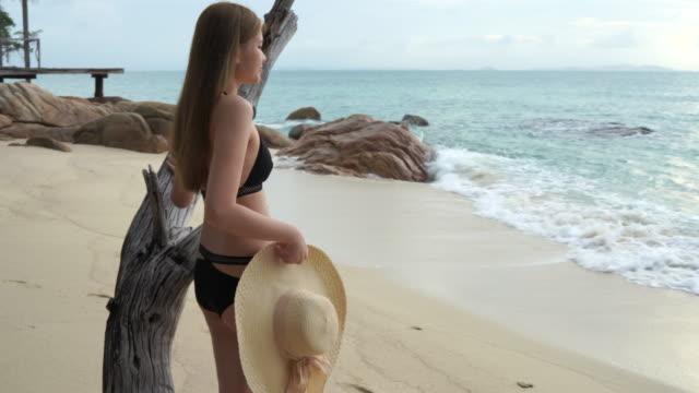 vídeos y material grabado en eventos de stock de mujer caminando en el desgaste de la playa bikini llevaba un sombrero de mar, el medio ambiente luminoso y claro. - espalda humana