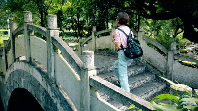 woman walk through traditional chinese arch bridge - arch bridge stock videos & royalty-free footage