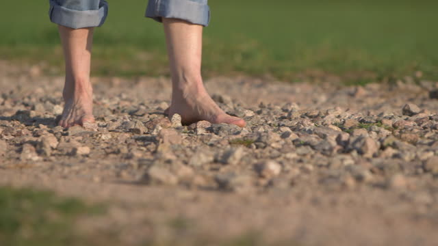 woman walking abaout stones with bare feets, close of feets, from the front